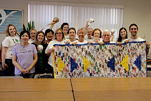 Volunteers at New Life for Old Bags displaying a completed sleeping mat made out of plastic bags to be given to homeless individuals in Chicago.