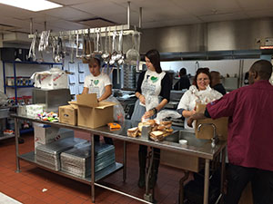 Some of the volunteers preparing food in the kitchen of the Salvation Army Harbor Light center.