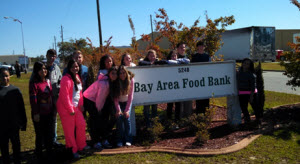 Adrienne's student pose for a photo after volunteering at a local food bank.